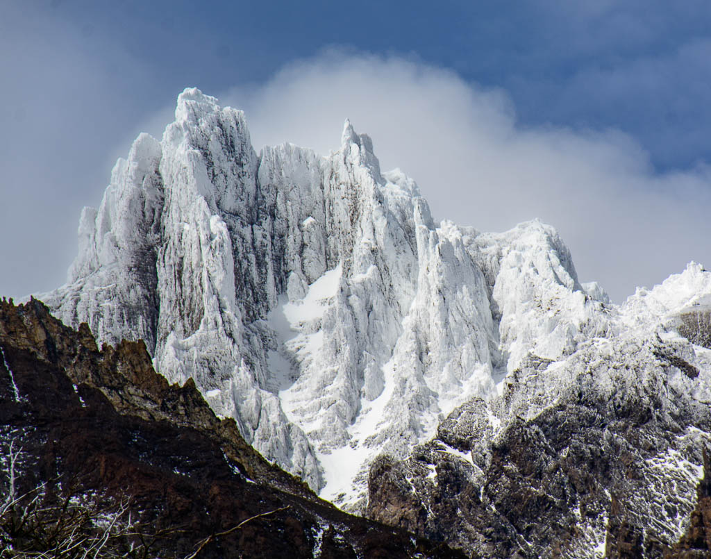Jagged, rocky, snow-covered mountains, bare of vegetation, against a blue sky